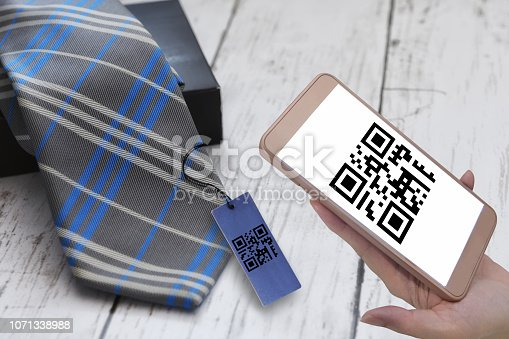 istock and holding smartphone with scanning QR code sign screen with necktie on white wooden background 1071338988