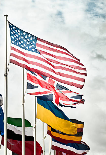 US UK and International Flags Several flags on display with an exaggerated, turbulent sky behind.  Partially desaturated image. diplomacy stock pictures, royalty-free photos & images