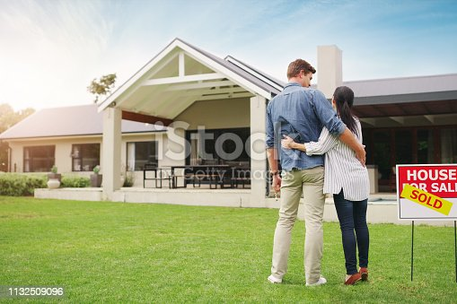 Shot of a young couple admiring their newly purchased house