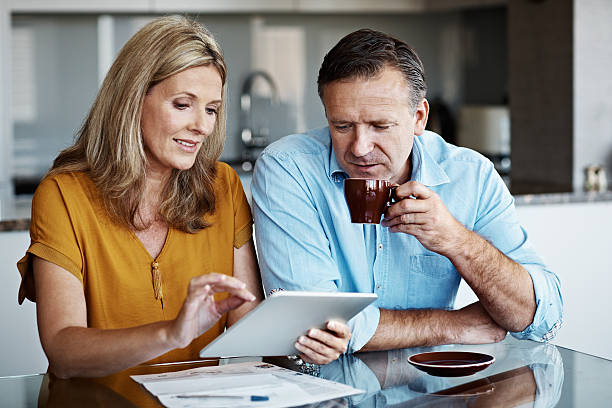 And it's as easy as 'enter'! Shot of a mature couple paying their bills online from home mature couple stock pictures, royalty-free photos & images