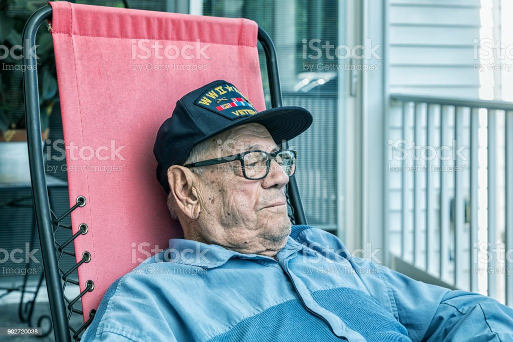 WWII and Korean Conflict Military Veteran Sitting Comfortably Relaxing stock photo