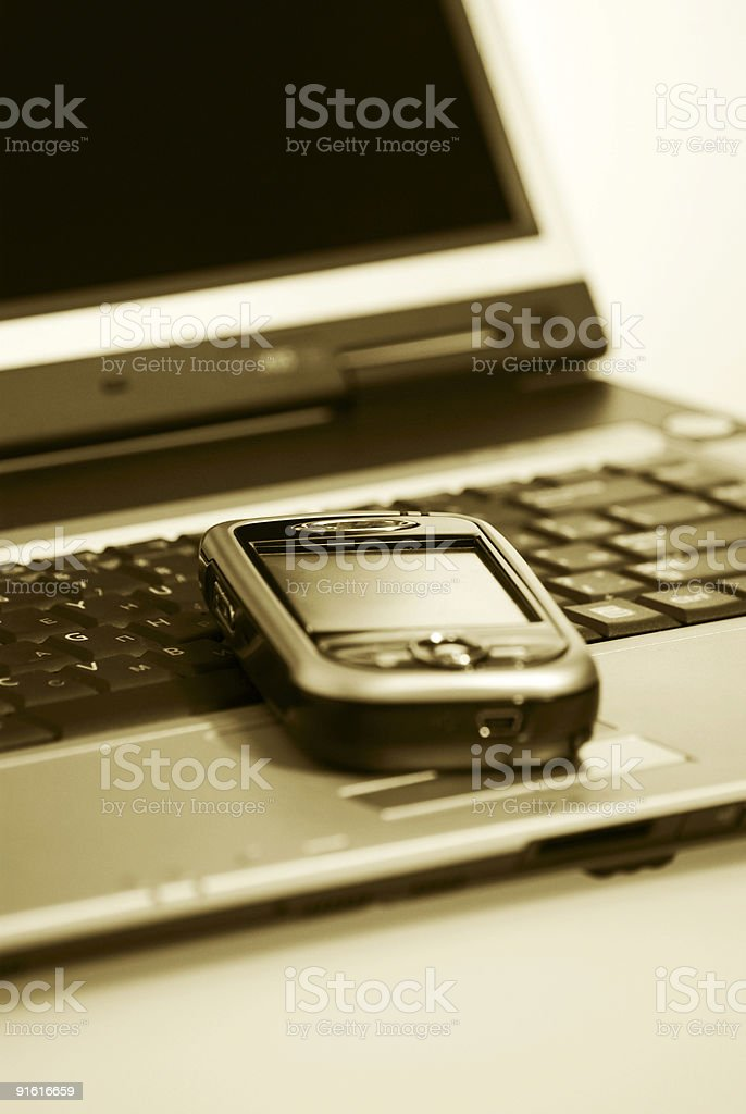PDA and laptop. Sepia. stock photo