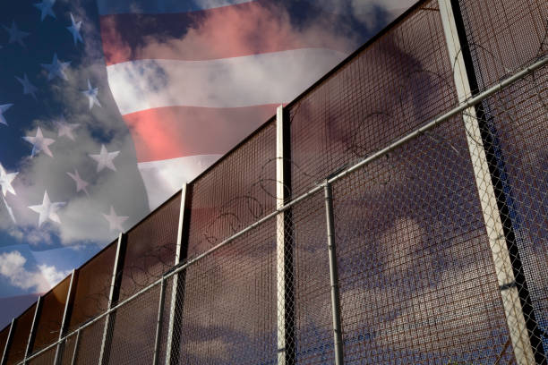 US and Mexico Border Fence and American Flag Composite stock photo