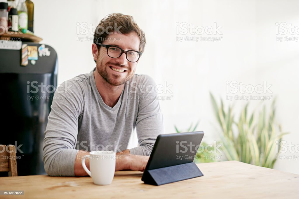 Portrait of a young man having coffee and using a digital tablet at...