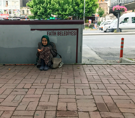Istanbul, Turkey - June 19, 2017: a very old woman asking for some money in front of a stone wall of Fatih Belediyesi (Municipality of Fatih) for helping panhandler asker aid human relations street city life concepts