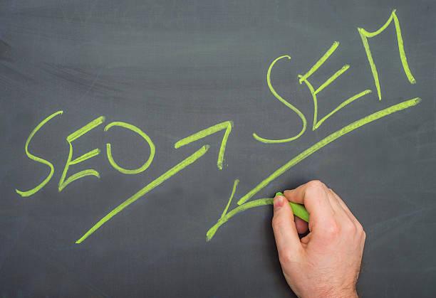 SEO and sem written on blackboard with hand Suchmaschinenoptimierung Suchmaschinenmarketing stock photo