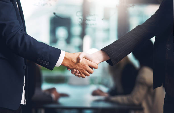 And so the deal was sealed Cropped shot of a businessman and businesswoman shaking hands in a modern office alliance stock pictures, royalty-free photos & images