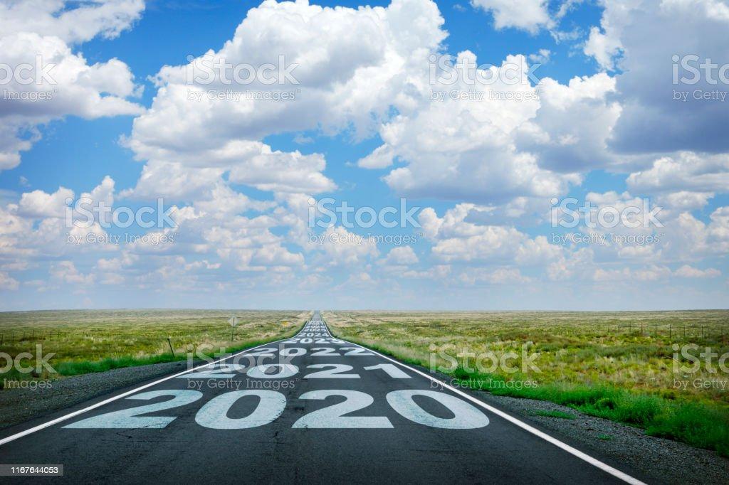 2020年とその後の日付は、長いまっすぐな田舎道に描かれました - 2020年のロイヤリティフリーストックフォト