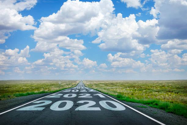 2020 And Subsequent Dates Painted On Long Straight Rural Road The year 2020 and subsequent years are painted on to a long straight rural highway that disappears at the horizon under a canopy of cumulus clouds. the way forward stock pictures, royalty-free photos & images