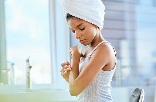 Shot of an attractive young woman applying moisturiser to her arms during her morning beauty routine