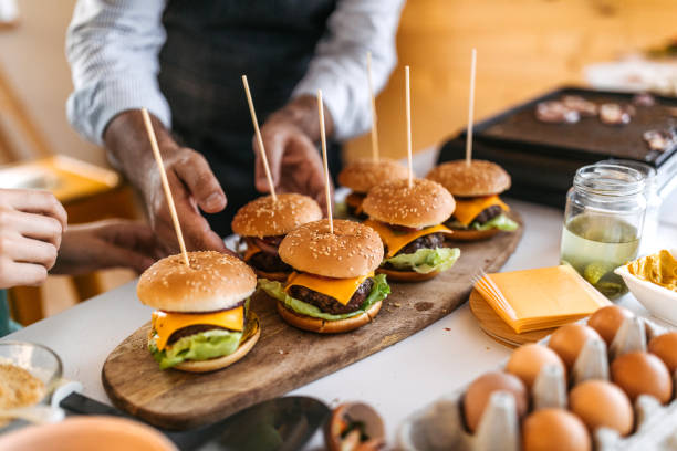 And that's  yummy cheeseburgers Mature man and his son finishing burgers  preparation at home slider burger stock pictures, royalty-free photos & images