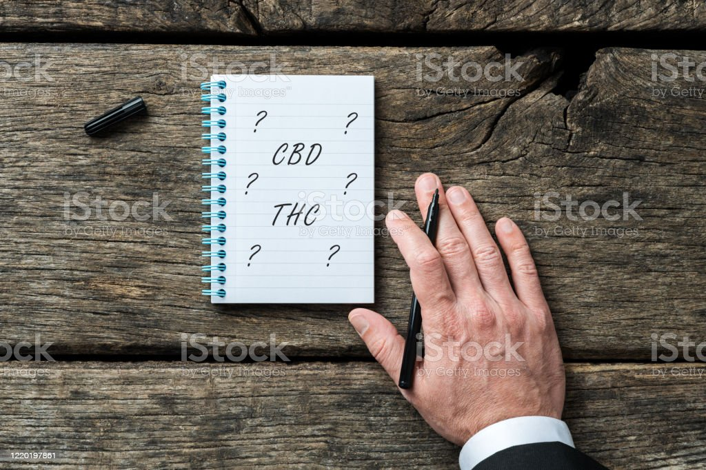 CBD and THC legalization conceptual image CBD and THC legalization conceptual image - hand of a lawyer writing THC and CBD in his notepad. Addiction Stock Photo