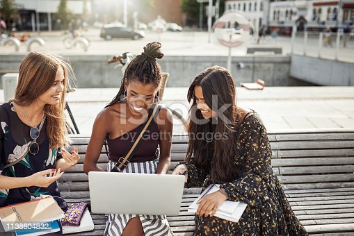 Shot of young women studying together outdoors