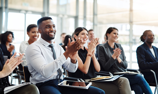 Shot of a group of businesspeople clapping during a conference