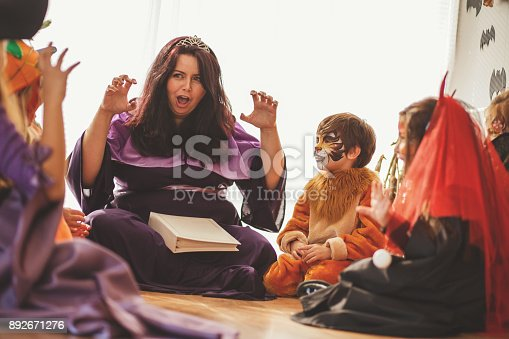 Woman is telling a story to group of children at the costume party.