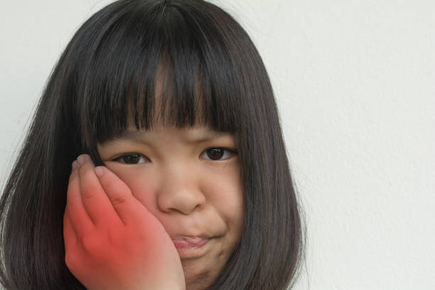 TMD and TMJ healthcare concept: Temporomandibular Joint and Muscle Disorder. Asia child kid girl hand on cheek face as suffering from facial pain, mumps or toothache TMD and TMJ healthcare concept: Temporomandibular Joint and Muscle Disorder. Asia child kid girl hand on cheek face as suffering from facial pain, mumps or toothache exocrine gland stock pictures, royalty-free photos & images