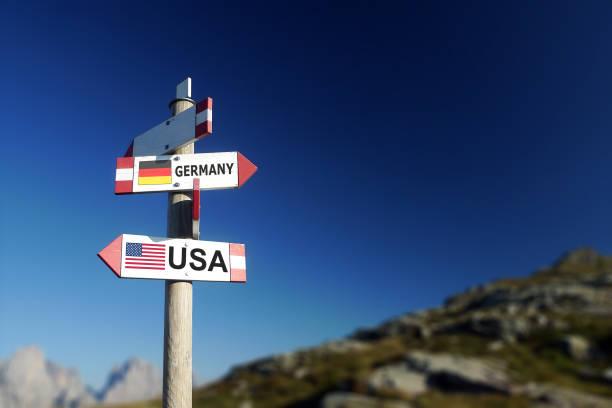 usa und usa flaggen auf wegweiser, politik-konzept - deutschland usa stock-fotos und bilder