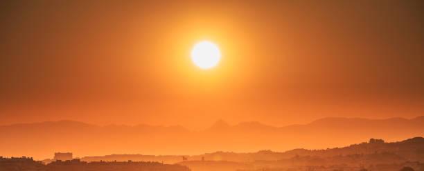 andalusien, spanien. soluppgång över sommarlandskap med mörka silhuetter av kullar, berg och bull statyer.  morgon solen skiner över spanska landskap nära costa del sol i malaga provinsen. - spain solar bildbanksfoton och bilder