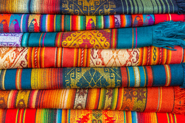 Andes Textiles in Otavalo, Ecuador A pile of colorful Andes textiles on the sunday art and craft market of Otavalo in Ecuador, north of Quito. peruvian culture stock pictures, royalty-free photos & images