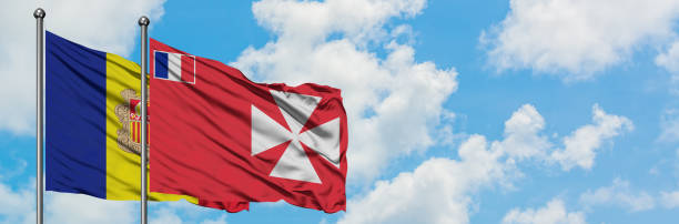 Andorra and Wallis And Futuna flag waving in the wind against white cloudy blue sky together. Diplomacy concept, international relations. stock photo