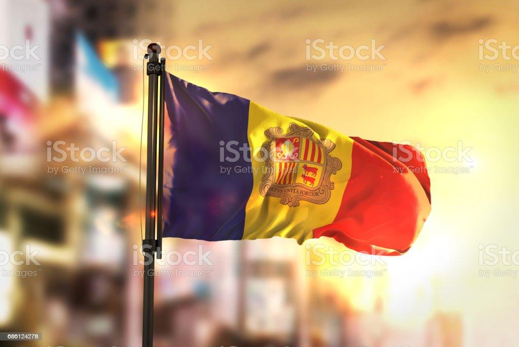 Bandeira de Andorra contra cidade turva fundo no Sunrise Backlight - foto de acervo