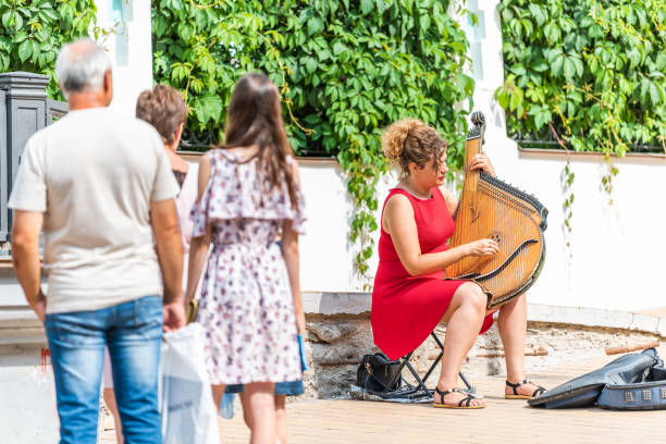 Cтоковое фото Andriyivskyy Uzviz Descent with woman playing on traditional harp guitar called Bandura in Kiev and people watching on street sidewalk in summer
