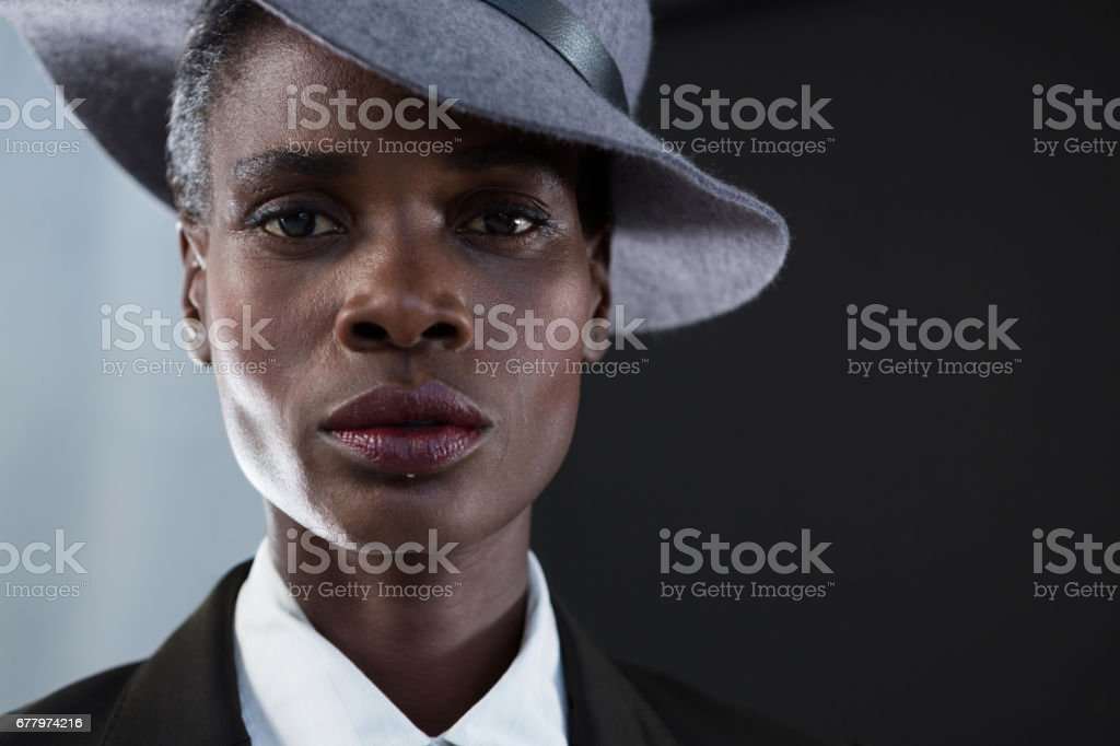 Androgynous man in hat against grey background royalty-free stock photo