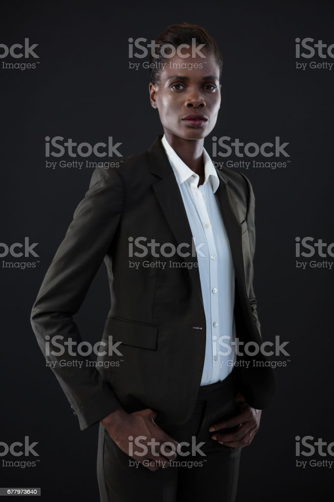 Androgynous man in suit posing against grey background royalty-free stock photo