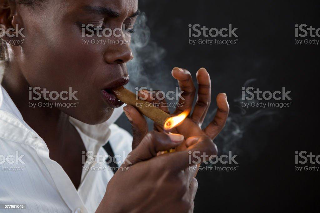 Androgynous man lighting a cigar stock photo