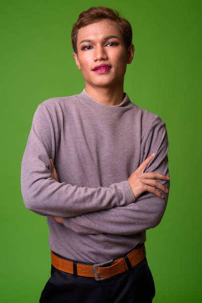 Androgynous young Asian man wearing makeup Studio shot of androgynous young Asian man wearing makeup transgender stock pictures, royalty-free photos & images