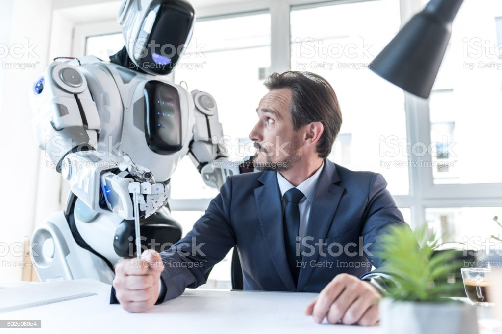 Android is standing near grumpy man stock photo