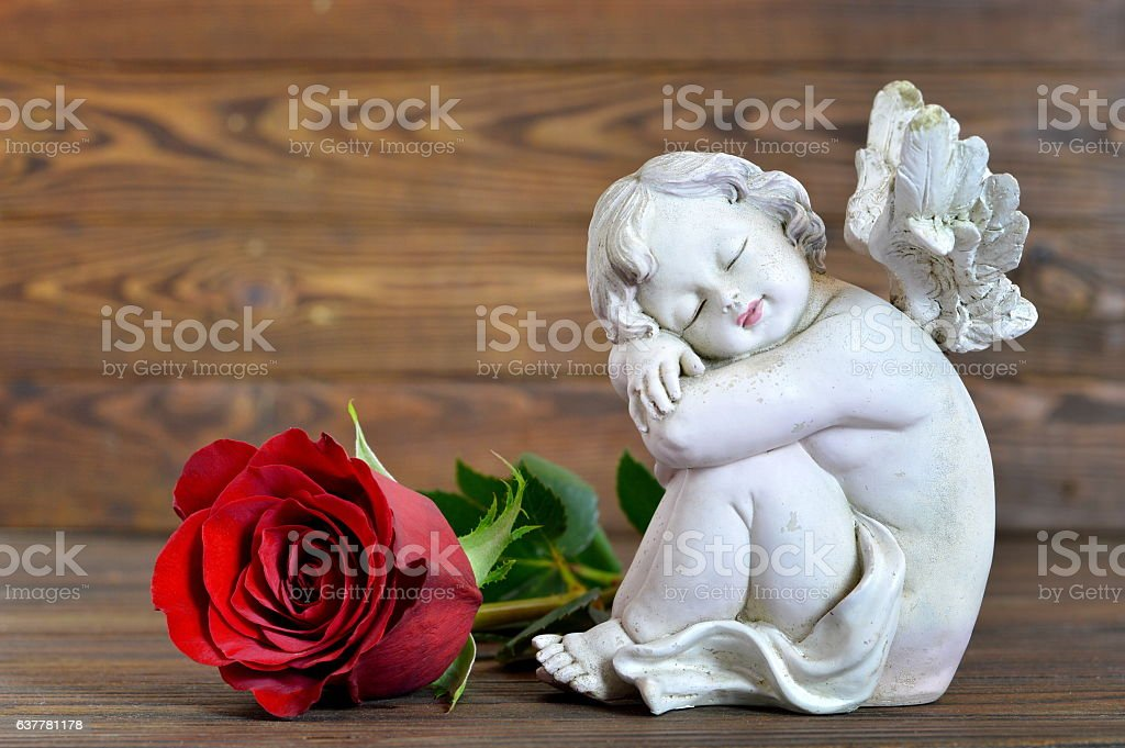 Angel and red rose on wooden background stock photo
