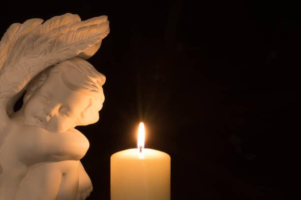 Angel and white burning candle stock photo
