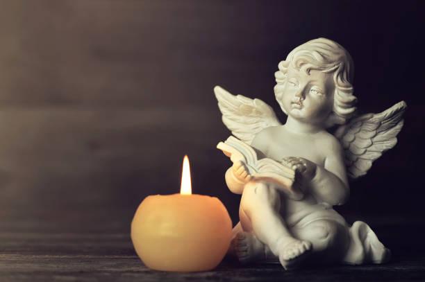 Engel und weiße Kerze auf dunklem Hintergrund. Schutzengel beim Lesen eines Buches – Foto