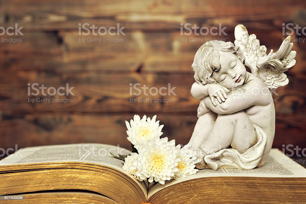 Angel and white flowers on old book stock photo