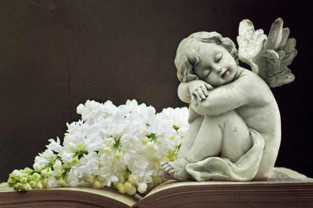 angel and white lilac flower on old book - funerale foto e immagini stock