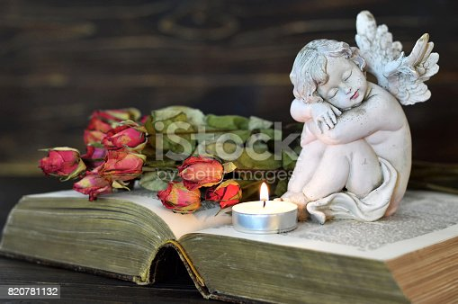 istock Angel, candle and dry roses on wooden background 820781132