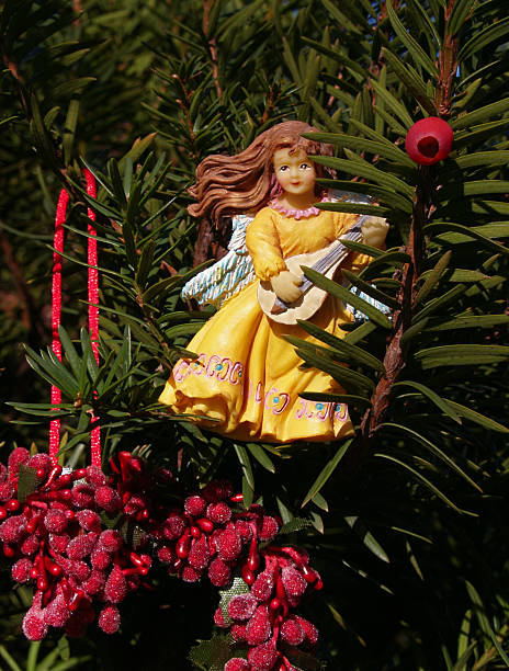 Angel Christmas Ornament in Gold with Lute and Red Berries stock photo