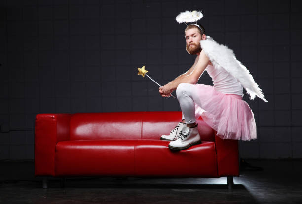 Angel: costume man sitting on couch stock photo