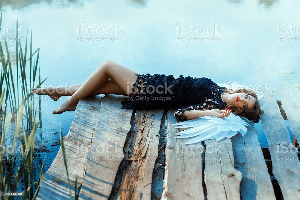 Angel girl lying on the pier. stock photo