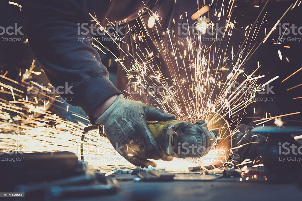 Angel grinder makes a flash of sparks while cutting stock photo