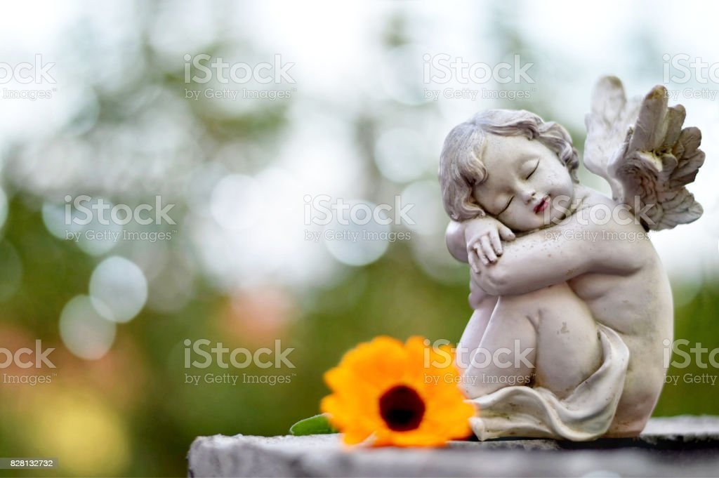 Angel guardian sleeping on the grave stock photo