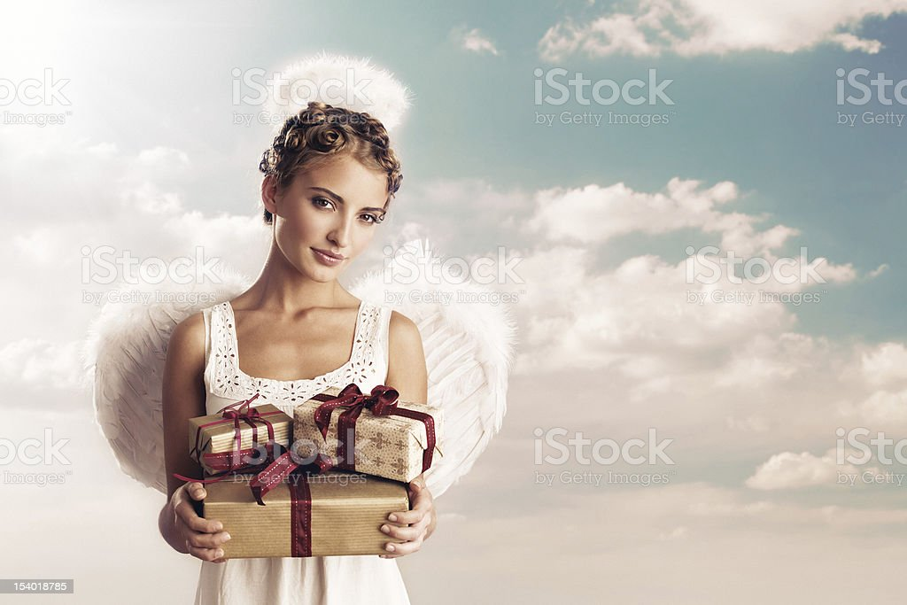 angel holding christmas gifts stock photo