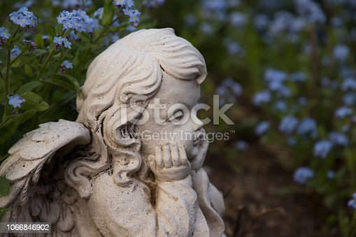 angel in garden with forget-me-not flowers