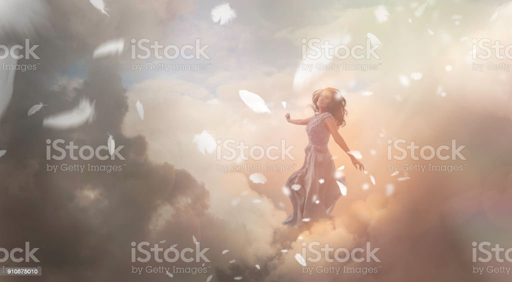 Angel in sky with falling feathers stock photo