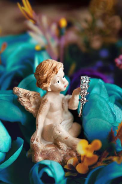 engel hält einen diamantring - schmuck engel stock-fotos und bilder