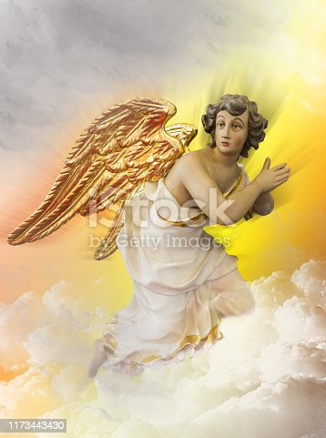 istock Angel kneeling on a cloud in heaven. Religious background. 1173443430