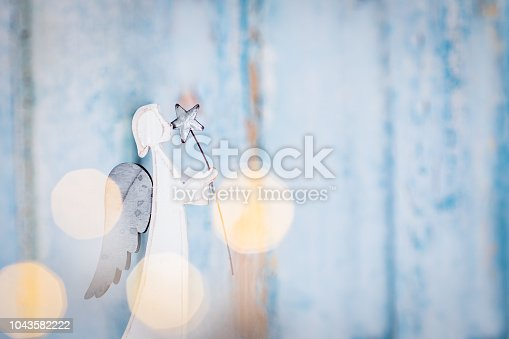 Blue festive background with a white angel holding a star