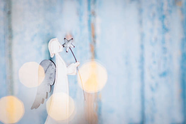 Angel on Christmas background Blue festive background with a white angel holding a star angelic stock pictures, royalty-free photos & images
