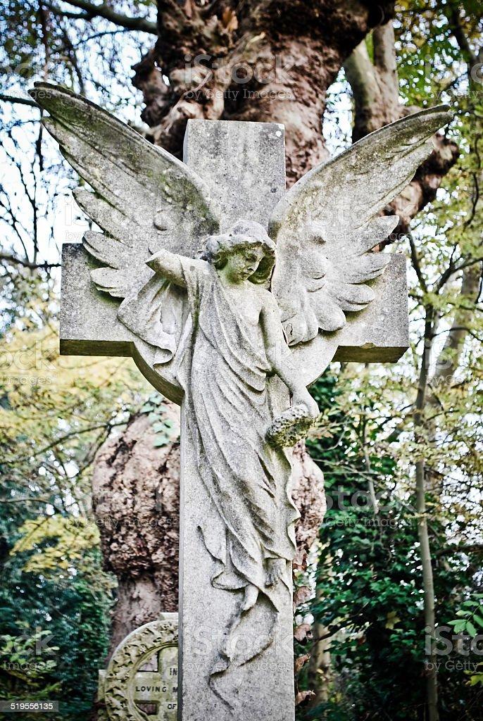 Angel on cross statue stock photo